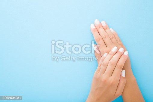 1147741037 istock photo Young woman hands with white nails on light blue table background. Pastel color. Point of view shot. Closeup. Soft touch. Empty place for text. Top down view. 1262694031