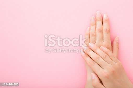 1147741037 istock photo Young woman hands without nail polish on light pink background. Pastel color. Simple manicure. Closeup. Empty place for text. Top down view. 1224964485