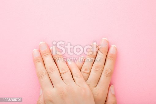 1147741037 istock photo Young woman hands without nail polish on light pink table background. Pastel color. Simple manicure. Closeup. Empty place for text. Top down view. 1223205701