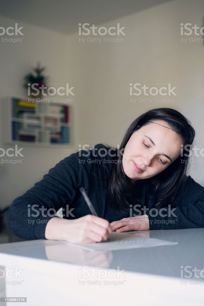 happy girl in her living room handwriting a lettere to her beloved...
