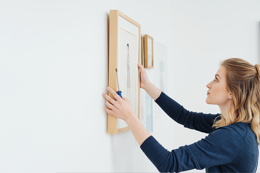 Young attractive blond woman hanging a picture in a plain wooden frame on a wall with a look of concentration and copy space