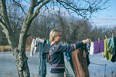 Blond woman hanging laundry to dry outdoors on a line hanging from a tree to the house. Retro style clothes