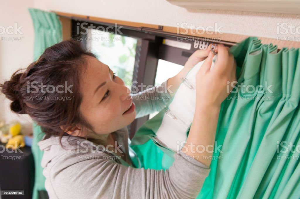 Young woman hanging curtain stock photo