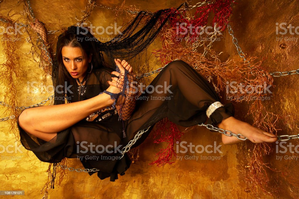 Young Woman Hanging From Wall with Chains royalty-free stock photo