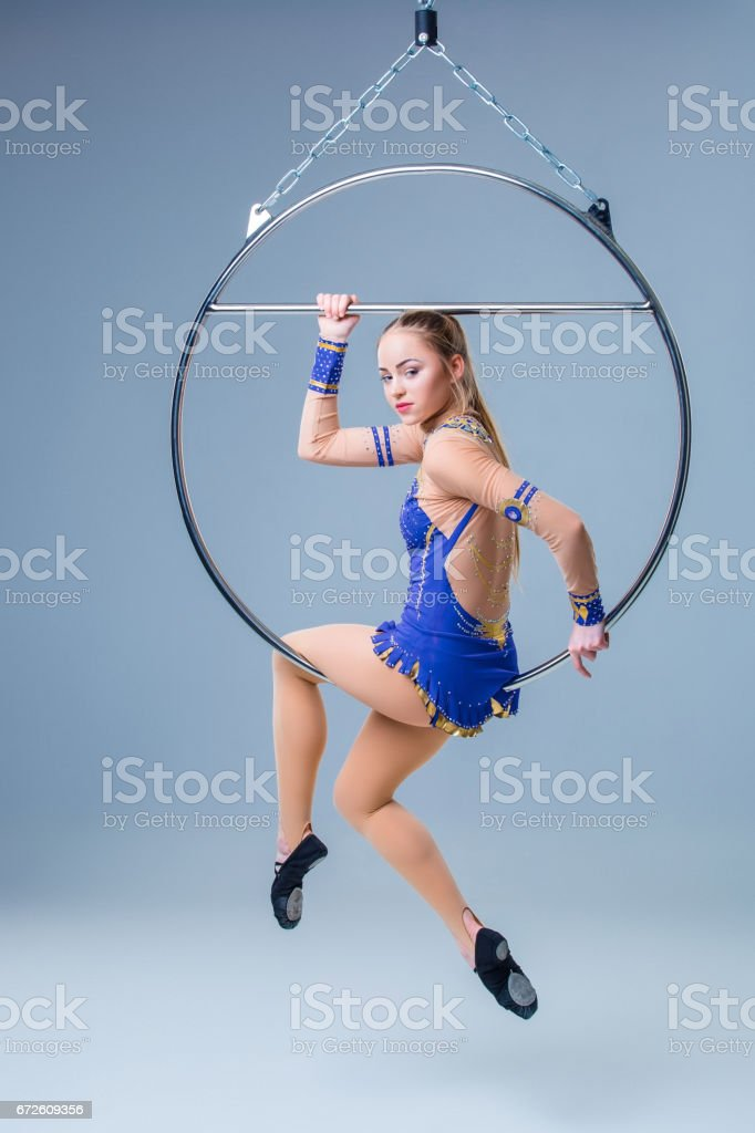 Young woman hanging in aerial ring on a blue background stock photo