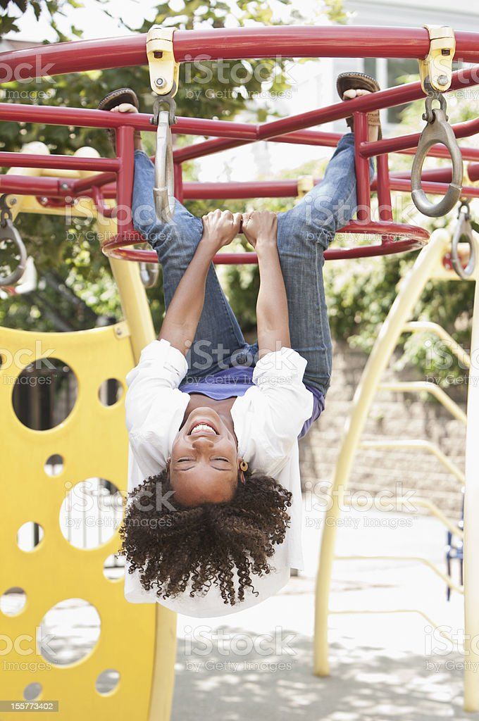 Young woman hanging n monkey bars royalty-free stock photo