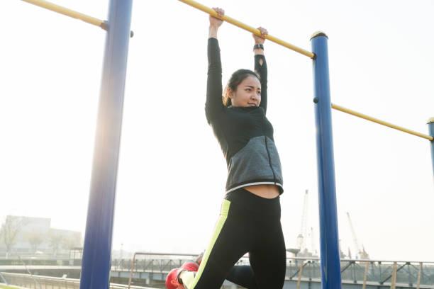 young woman hanging on horizontal bar - horizontal bar stock photos and pictures