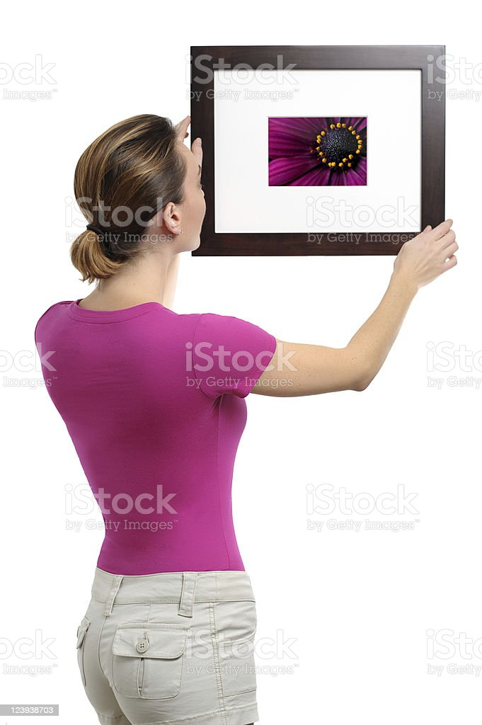 Young Woman Hanging Picture of Flower Isolated on White Background royalty-free stock photo