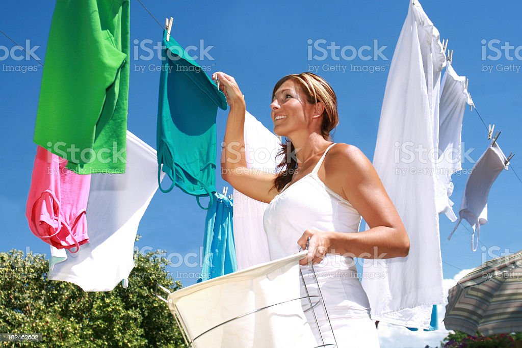 Young woman hanging up laundry stock photo