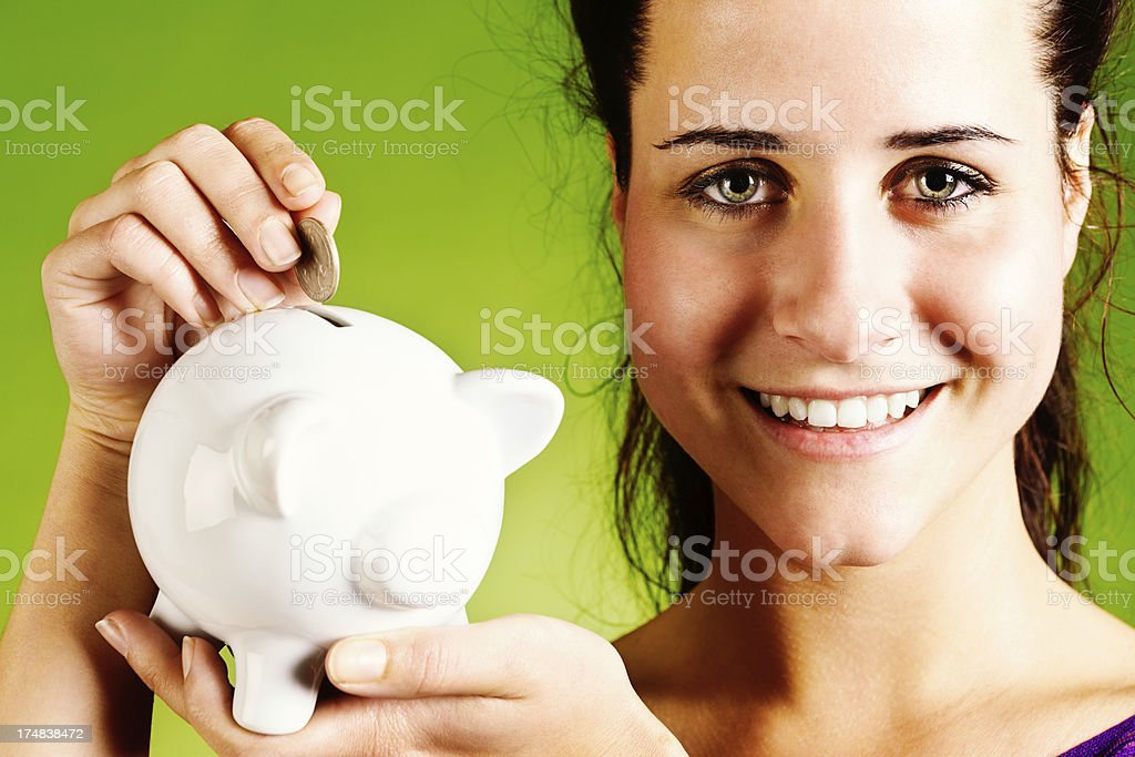 Young woman happily saving money in piggybank royalty-free stock photo