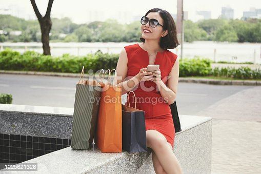 Smiling elegant young woman resting in park after shopping in mall and checking social media on smartphone
