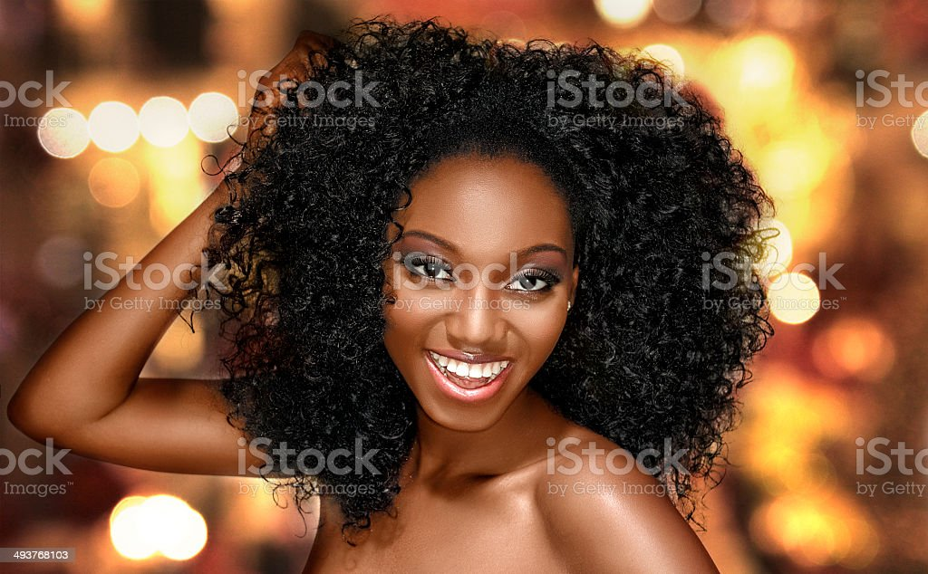 Young woman happy with curly hair on a bright background stock photo