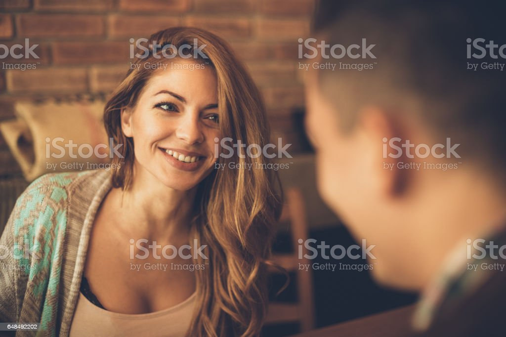 Young woman has a big smile while looking at a man at a table in a cafe stock photo