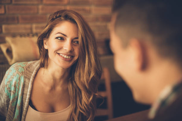 Young woman has a big smile while looking at a man at a table in a cafe - Photo