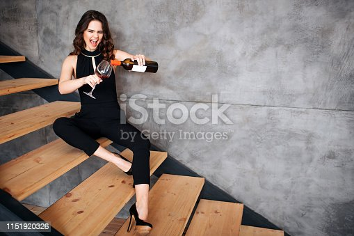 Young woman has problems with alcohol. Stylish model sitting on steps and pouring wine into glass. Emotional brunette having fun