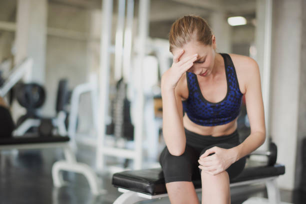 junge frau haben muskelschmerzen am knie beim training im fitnessstudio. frau kopfschmerzen.  unfall-gewichtstraining bei fitness, muskelschmerzkonzept. - mit muskelkater trainieren stock-fotos und bilder