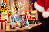 istock Young woman having a Christmas video call with her happy family. Concept of families in quarantine during Christmas because of the coronavirus. Xmas still life with a tablet in a cozy room 1287056663