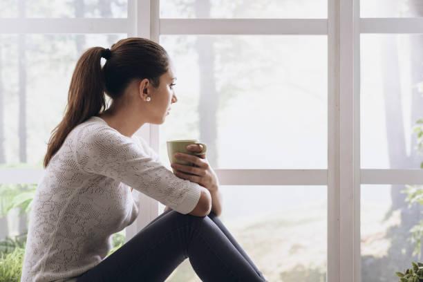 Junge Frau, die eine Kaffeepause zu Hause, sie sitzt neben einem Fenster und trinken – Foto