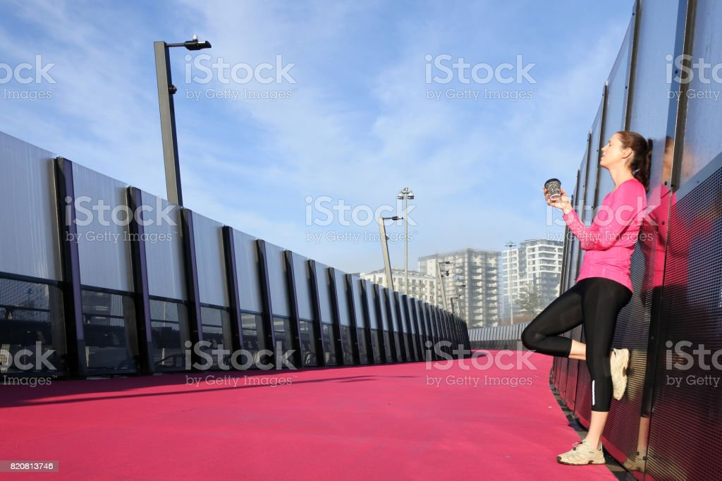 Young woman having a coffee break on a bright pink road stock photo