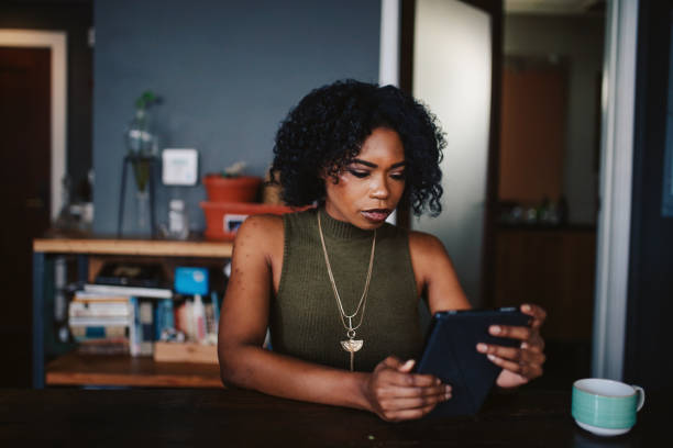 Young woman having a coffee in her apartment while browsing the web on tablet stock photo