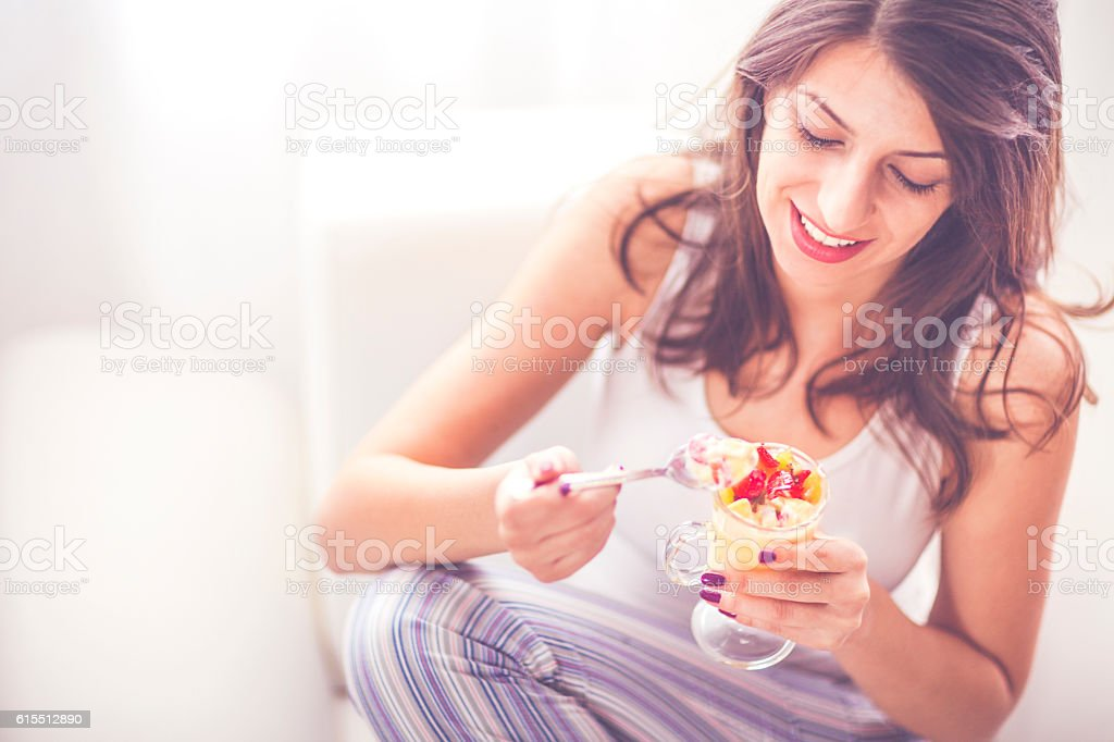 Young woman having a fruit salad stock photo