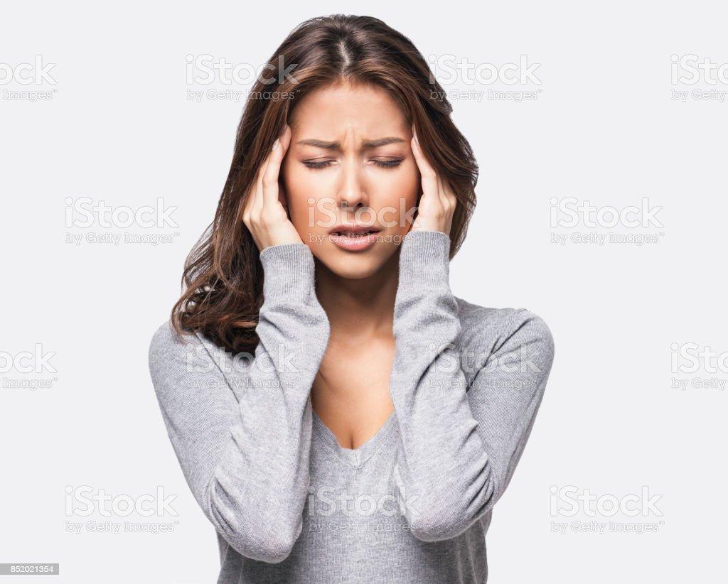 Mujer joven teniendo un dolor de cabeza - foto de stock