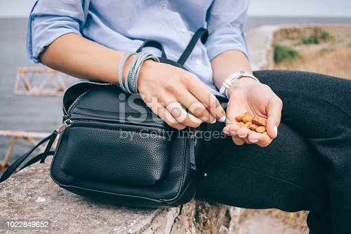 Young woman having a healthy snack, while sitting on a parapet near the sea. Female's hand holding a handful of almonds next to an open bag, close-up.