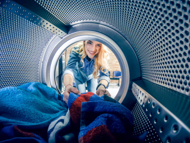 Young woman having a laundry day Young woman doing laundry hes weekly washing in a self-service public laundry. View from the washing machine laundry detergent stock pictures, royalty-free photos & images