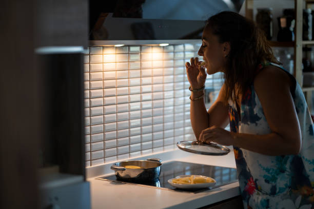 Young woman having a midnight snack Young woman having a midnight snack midnight stock pictures, royalty-free photos & images