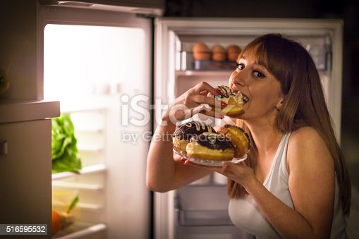 istock Young woman having a midnight snack 516595532