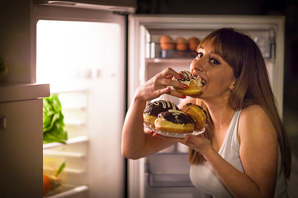 Young woman having a midnight snack Close up image of a young woman with eating disorder, having a midnight snack - eating donuts, in front of the refrigerator. temptation stock pictures, royalty-free photos & images