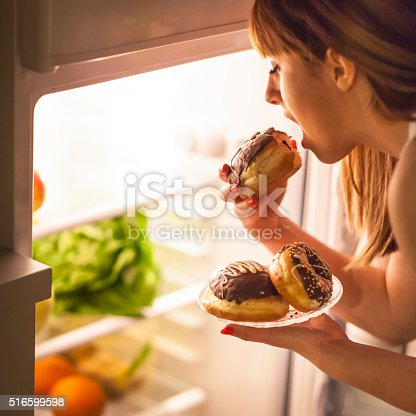 istock Young woman having a midnight snack 516599598