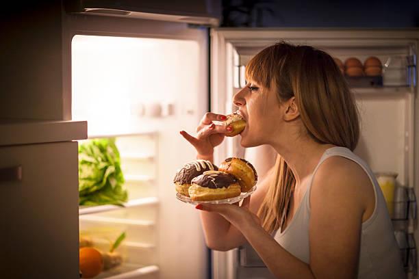 young woman having a midnight snack - 不健康飲食 個照片及圖片檔