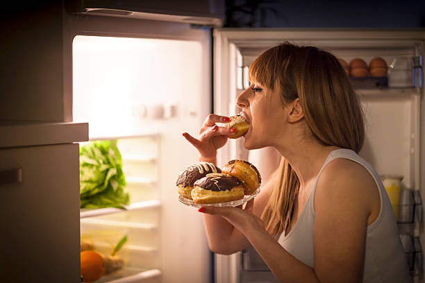 Young woman having a midnight snack Close up image of a young woman with eating disorder, having a midnight snack - eating donuts, in front of the refrigerator. unhealthy eating stock pictures, royalty-free photos & images