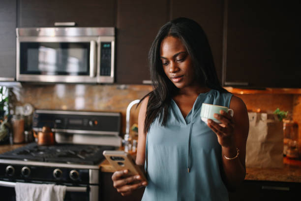 Young woman having a morning coffee in her Downtown Los Angeles apartment stock photo