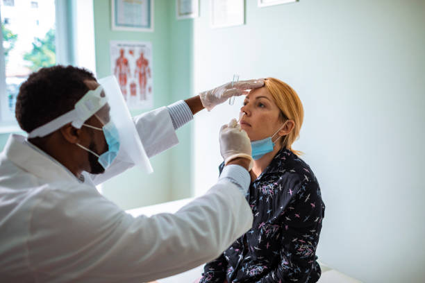Young woman having a nasal swab test Close up of a young woman having a nasal swab test done by his doctor medical test stock pictures, royalty-free photos & images