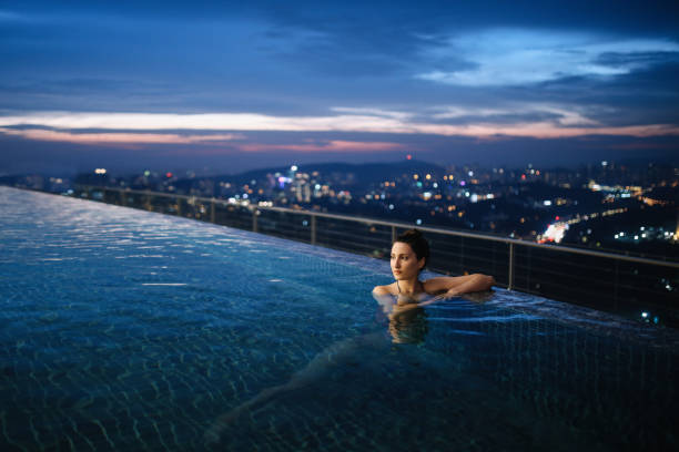 Young woman having a night swim in the pool in Malaysia Young brunette woman relaxing in the pool, swimming on top of the building in Kuala Lumpur, Malaysia. She is having a moment to relax after work in the busy city of Kuala Lumpur, Malaysia. upper class stock pictures, royalty-free photos & images