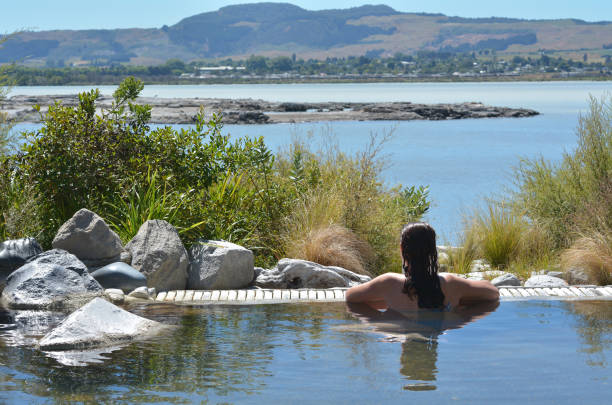 Young woman having a spa Young woman having a spa in outdoors hot pool in Rotorua, New Zealand. rotorua stock pictures, royalty-free photos & images