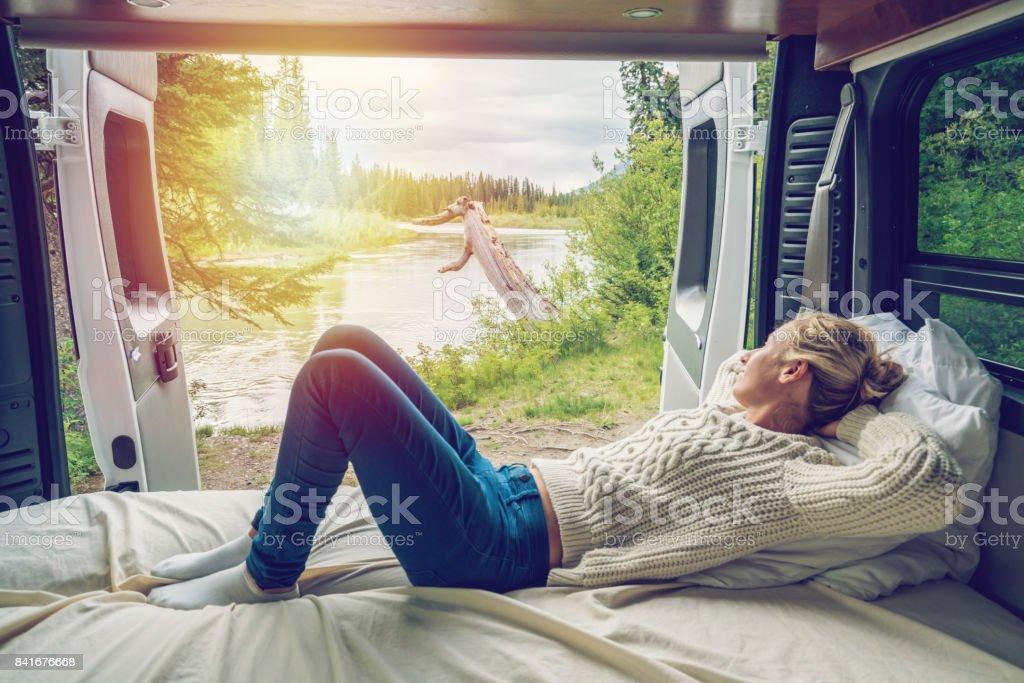 Junge Frau, die einen atemberaubenden Blick aus dem hinteren Teil ihres Camping-Van – Foto