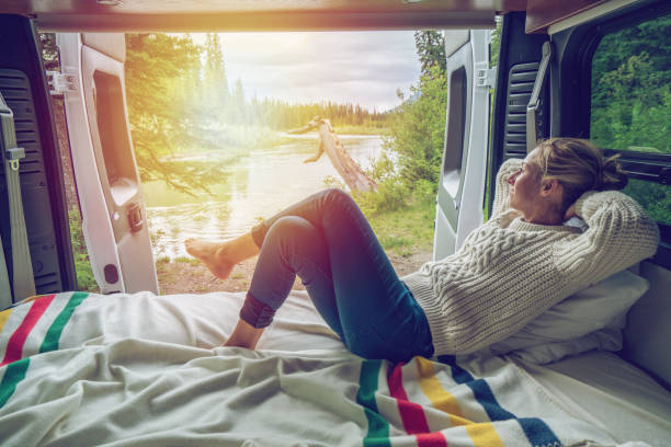 Young woman having a stunning view out of the back of her Camping Van stock photo