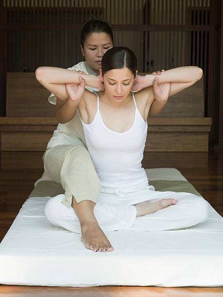 young woman having a thai massage - thai massage stock photos and pictures