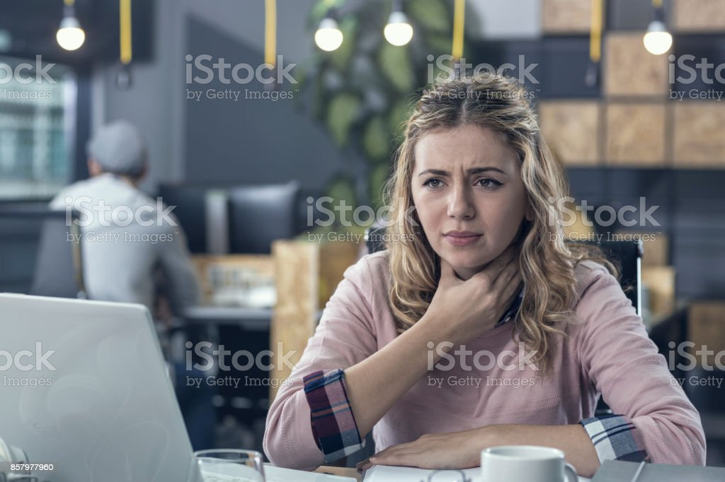 Young woman having a throat ache at work stock photo