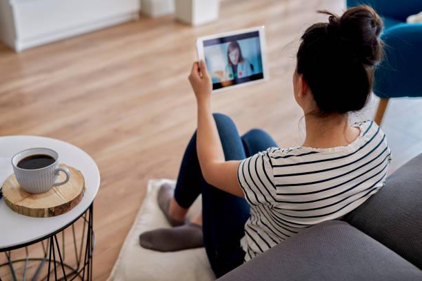 mujer joven que tiene una videoconferencia con su médico - telehealth fotografías e imágenes de stock