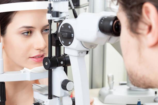 眼科クリニックでテスト細隙灯目を持つ若い女性 - 検眼医 ストックフォトと画像