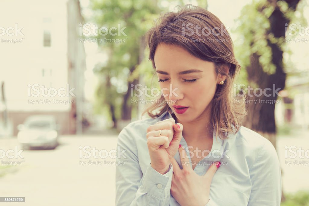Young woman having asthma attack or choking can't breath suffering from respiration problems standing outdoors on a urban street stock photo