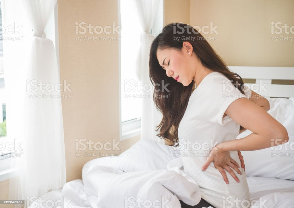 Young woman having back ache sitting on white bed. stock photo