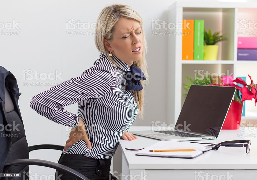 Young woman having back pain at work stock photo