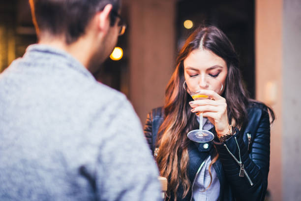 Young woman having bad date Young brunette woman sitting at a bar and having a conversation with a guy. bad date stock pictures, royalty-free photos & images