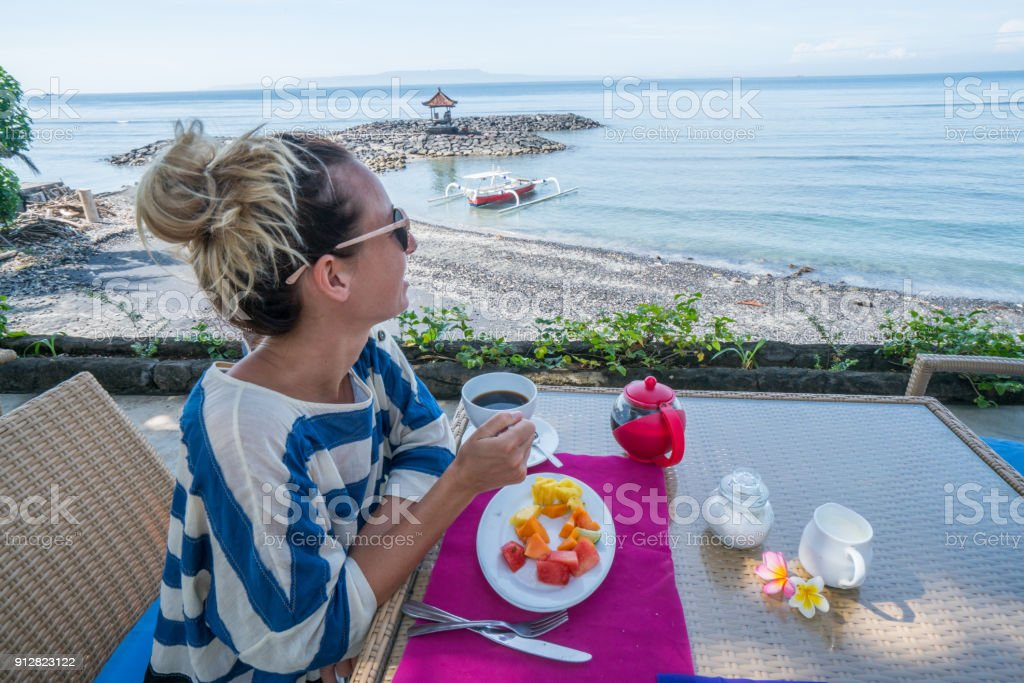 Caucasian female enjoying breakfast in the morning by the sea from...