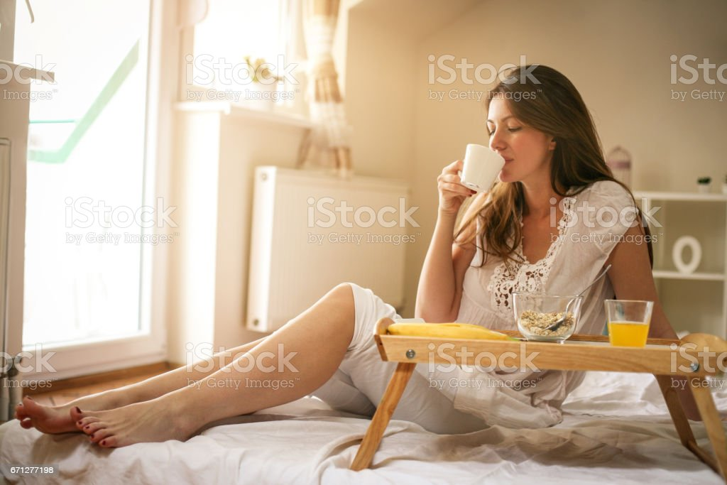 Young woman having breakfast in bed. stock photo